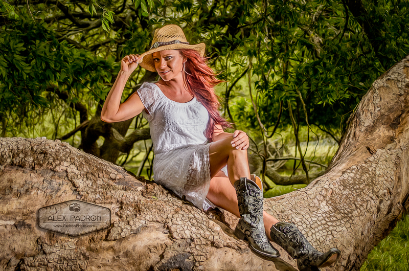 girl in cowboy boots sitting on tree