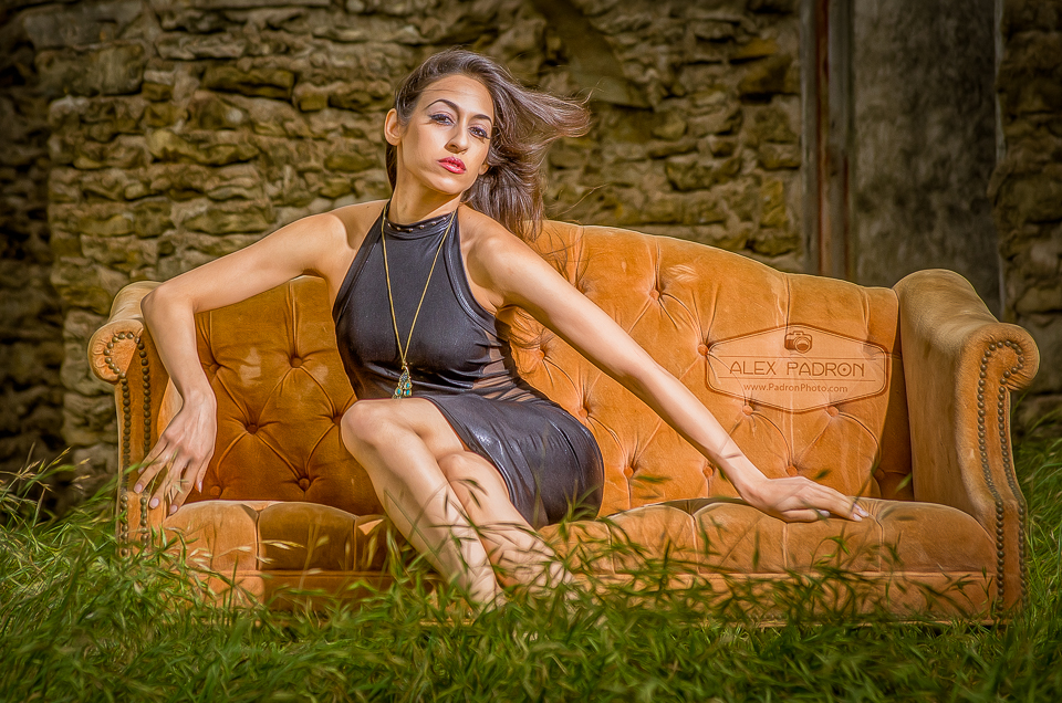 model on outdoor orange couch in grassy field